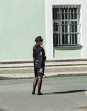 Girl in russian police uniform stands against the wall of the He Royalty Free Stock Photography