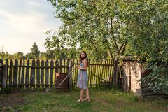 A girl in a rustic old-fashioned dress goes holding a rake over a rural garden courtyard. A teen girl in a rustic old-fashioned dress goes holding a rake over a royalty free stock images