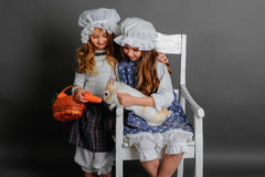 Girl in a rustic style with the Easter bunny. Carrot and basket Stock Photos