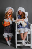Girl in a rustic style with the Easter bunny. Laughing girl in a rustic style with the Easter bunny, carrot and basket Stock Photos
