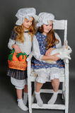 Girl in a rustic style with the Easter bunny. Smiling girl in a rustic style with the Easter bunny, carrot and basket Royalty Free Stock Photos
