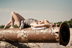 Girl on rusty pipe Stock Photo
