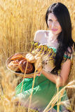 Girl in rye field with basket of buns and rolls Stock Photo