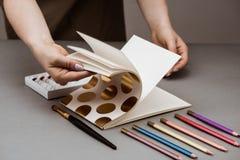 Girl& x27; s übergibt Öffnung Sketchbook Ölfarben, Bleistifte auf grauer Tabelle Stockfotografie