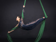 Girl`s aerial acrobatics in the paintings. Dark background. Studio photography of circus performers Stock Image