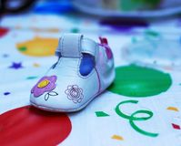 Girl`s baby shoe with flower accents. Girl`s baby shoe on a colorful mat with pink Royalty Free Stock Photography