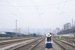 A girl`s back and the railway. The girl`s back and the broad railway junction station. The lonely figure of a girl royalty free stock photos