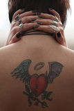 Girl's back tattoo. Girl holding her hands on her neck, having a tattoo on her back royalty free stock photo