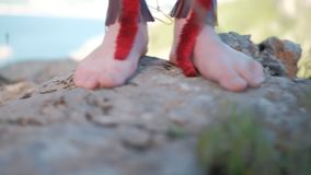 Girl`s bare feet on the rocks. Girl`s bare feet in native american acsessories on the rocks stock footage