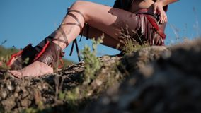 Girl`s bare feet on the rocks. Girl`s bare feet in native American acsessories on the rocks stock video footage