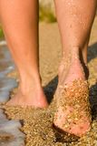Girl's barefoot feet in sea surf. Girl's barefoot feet on beach in sea surf Royalty Free Stock Images