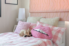 Girl's bedroom in pink color with pillows and doll Stock Photos