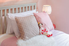 Girl's bedroom in pink color tone with doll on bed Royalty Free Stock Photos