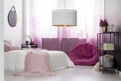 Girl`s bedroom with pink pouf. Designer lamp in girl`s bedroom with pink pouf against gradient curtains and mirror above bed Stock Images