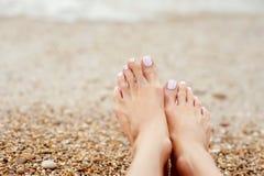 Girl& x27; s-ben på färgrika kiselstenar stranden vid havet Royaltyfri Foto