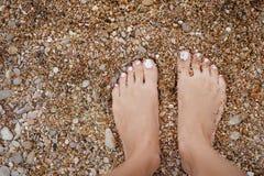 Girl& x27; s-ben på färgrika kiselstenar stranden vid havet Royaltyfri Fotografi