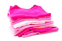 Girl's clothes. A heap of freshly washed and ironed pink girl clothes isolated on white studio background Royalty Free Stock Image