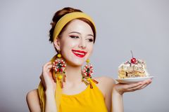 Girl in 70s clothes style with cake. Young redhead girl in 70s clothes style with cake on grey background stock photo