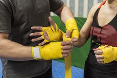 The girl`s coach bandages her hands under the boxing gloves. royalty free stock images