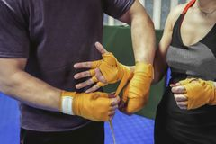 The girl`s coach bandages her hands under the boxing gloves. stock image