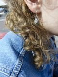 Girl`s curls and earring. royalty free stock images