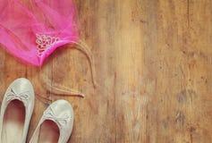Girl's diamond tiara with pink chiffon vail next to ballet shoes. Girl's diamond tiara with pink  chiffon vail next to ballet shoes on wooden background. vintage Stock Images
