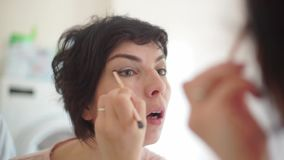 Girl`s does eye makeup. Girl does makeup close up stock video footage