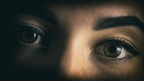 Girl`s eyes close portrait of horror from the shadows stock image