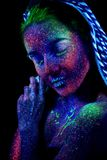 The girl`s face, aliens asleep. Hands near the face, ultraviolet make-up. Vertical. Beautiful royalty free stock image