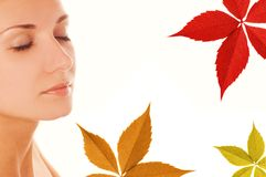 Girl's face and autumn leaves. Beautiful girl's face and colorful autumn leaves around her Royalty Free Stock Photo