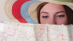 Girl's face behind a map. Woman looks at the map. Explore the country's vastness. Young tourist on vacation stock video footage