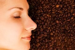 Girl's face and a coffee. Beautiful girl's face on over coffee bean background Stock Photography