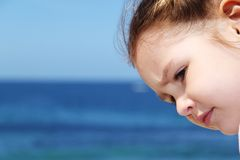 Girl's face with deep blue ocean backgroun. Girl's face with deep blue ocean and sky background Royalty Free Stock Photo