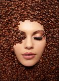 Girl's face drowned in coffee beans Stock Photo