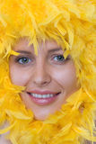 Girl's face in a frame of yellow feathers Stock Image