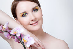 Girl's face and orchid Royalty Free Stock Images