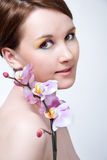 Girl's face and orchid Stock Images