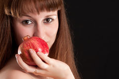 Girl's face and red pomegranate Royalty Free Stock Images
