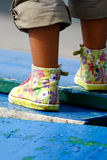 Girl?s feet. Outdoor female feet with flowered shoes on old blue wood Royalty Free Stock Photos