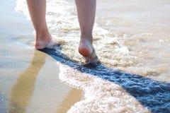 Girl`s feet on the beach. Sea waves and legs stock photos
