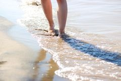 Girl`s feet on the beach. Sea waves and legs royalty free stock images