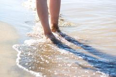 Girl`s feet on the beach. Sea waves and legs royalty free stock photography