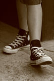 Girl's feet in converse sneakers (3). Girl in converse sneakers posing, sepia vintage retro style Royalty Free Stock Photo