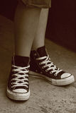 Girl's feet in converse sneakers. Girl in converse sneakers posing, sepia vintage retro style Stock Image