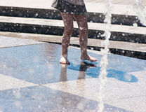 Girl's feet in gray skirt playing in the fountain Stock Photo