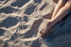 Girl's feet on sand Stock Image