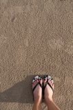Girl`s feet wearing sandals Which stood on the sand on the beach royalty free stock image