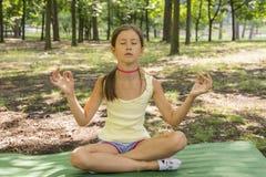 girl& x27; s feliz y reflexiona sobre la práctica de la yoga en el parque, niño de la yoga Forma de vida sana - niña que hace yog fotografía de archivo