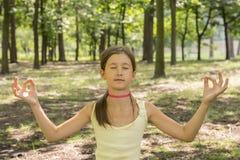 girl& x27; s feliz y reflexiona sobre la práctica de la yoga en el parque, niño de la yoga Forma de vida sana - niña que hace yog imagenes de archivo