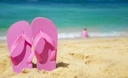 Girl's Flip flops on sandy beach. Flip flops on sandy beach with playing girl by the sea on background (Hawaii, Kauai Stock Photo